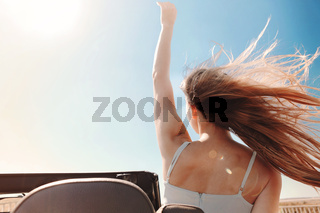 Happy woman sitting on passenger seat in car