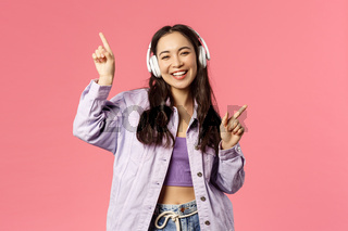 Lifestyle, technology and people concept. Portrait of carefree pretty young asian girl having fun, dancing joyfully, listening music in eadphones, raising hands up, singing along, pink background