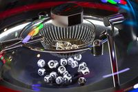 Black and white lottery balls in a rotating bingo machine. Number 16