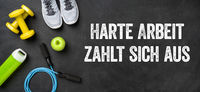 Fitness equipment on a dark background - Hard work pays off - Harte Arbeit zahlt sich aus (German)