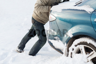 closeup of man pushing car stuck in snow
