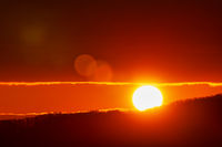 Beautiful sunrise in mountains, red sun disk rises from tops of mountain range. Natural lens flare in sky