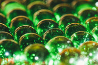 an array of green glass balls covered with dirt and dust and chips from old age