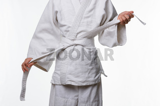 Stages of correct tying of the belt by a teenager on a sports kimono, step seven