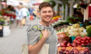 man with reusable shopping bag at street market