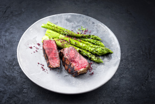 Barbecue dry aged wagyu roast beef steak with green asparagus and herbs as closeup on a modern design plate with copy space