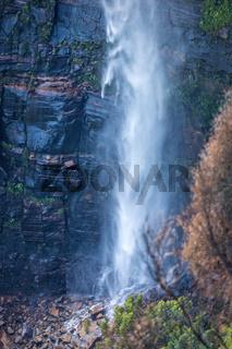 Waterfall tumbling down onto boulders at its base