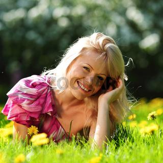 girl lying on the field of dandelions