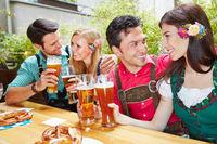 Zwei Paare trinken Bier im Biergarten zusammen