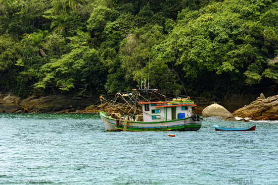 Fishing trawler anchored along the rocks and forest by the sea