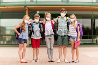 group of students in masks hugging over school