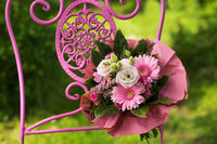 Pink flower bouquet on a garden chair