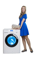 woman in a dress with a stack of towels next to a new washing machine