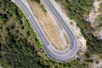 Aerial view of winding road in high mountain pass trough green pine woods.