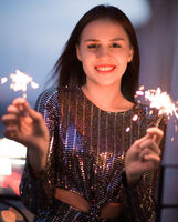 Delighted young lady smiling and waving burning sparklers during holiday celebration at night