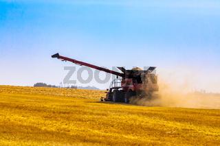 Combine harvester at work in crop field