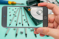 Computer hard drive on smartphone screen.  Set of screwdrivers for repair. Computer repair. Computer hard drive.