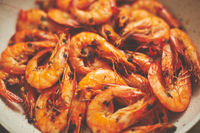 Close up of tasty fried whole prawns with parsley sprigs and garlic. Delicious seafood concept