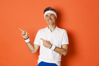 Portrait of active and healthy man doing sports, wearing activewear, smiling and pointing fingers left at workout promo, standing over orange background