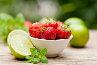 fresh tasty sweet strawberries and green lime outdoor in summer
