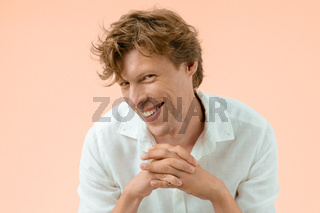 Smiling cheerful handsome man with his hands put together preparing a new important step. Confident man freelancer posing isolated on peach background