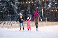 happy family at outdoor skating rink in winter