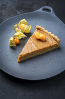 Traditional French Tarte au citron piece with orange and physalis fruit offered as closeup on a modern design plate