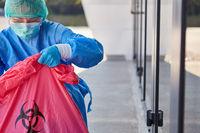 Reinigungskraft kontrolliert Entsorgung von Sondermüll in Klinik