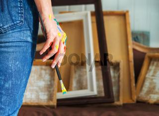 Closeup of an artist hand holding paintbrush