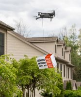 Drone delivering a coronavirus home test kit to residential house