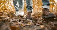 Couple In Jeans Walking Along Autumn Leaves