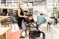 Young couple with newborn in stroller shopping at retail furniture and home accessories store wearing protective medical face mask to prevent spreading of corona virus when shops reopen.