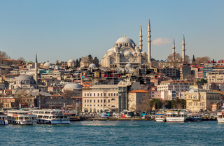 Istanbul, Turkey, 22 March 2019: View to Eminonu pier and Suleymaniye mosque across Bay of Golden Horn on sunny morning. Touristic sightseeing ships in Golden Horn bay of Istanbul