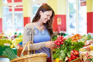 Frau kauft Radieschen im Supermarkt