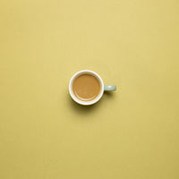 Cup of coffee on khaki background. top view, copy space