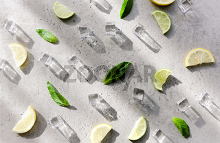 Fresh mint leaf and ice cubes with droplets and lime on background