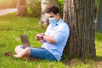 Man in protective mask is working with laptop outdoor, during Coronavirus pandemic outrbreak.