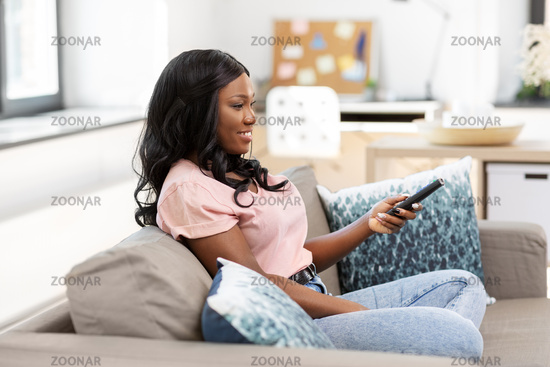 happy african american woman watching tv at home