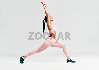 Young sporty woman doing yoga asana Warrior I Pose on white background.