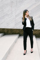 Smiling businesswoman in suit. Businesswoman talking phone outdoors