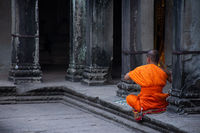 A lone monk in bright orange robes prays at an ancient temple, Angkor Wat, Cambodia.
