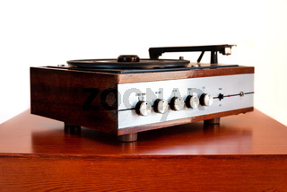 Vintage turntable made of wood on a old table