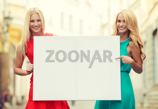 two happy blonde women with blank white board