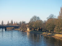 the river ouse in york with people sat along the banks in afternoon sunlight