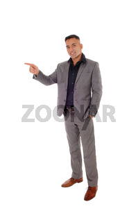 Young man standing in gray suit pointing with finger