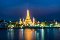 Illuminated temple of Dawn or Wat Arun in Bangkok at sunset