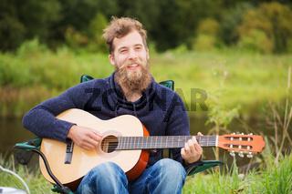 smiling man playing guitar in camping