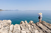 Woman traveler wearing straw summer hat and backpack, standing at edge of the rocky cliff looking and pointing at big blue sea and islands in on the horizon
