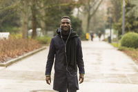 Portrait of Young Black Man with Earphones and Posing on Park Road