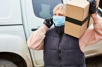 Paketbotin mit Mundschutz ruft Empfänger an